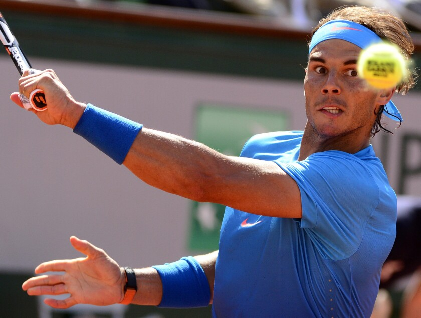 Rafael Nadal prepares to hit a backhand during a French Open quarterfinal match against Novak Djokovic at Roland Garros.