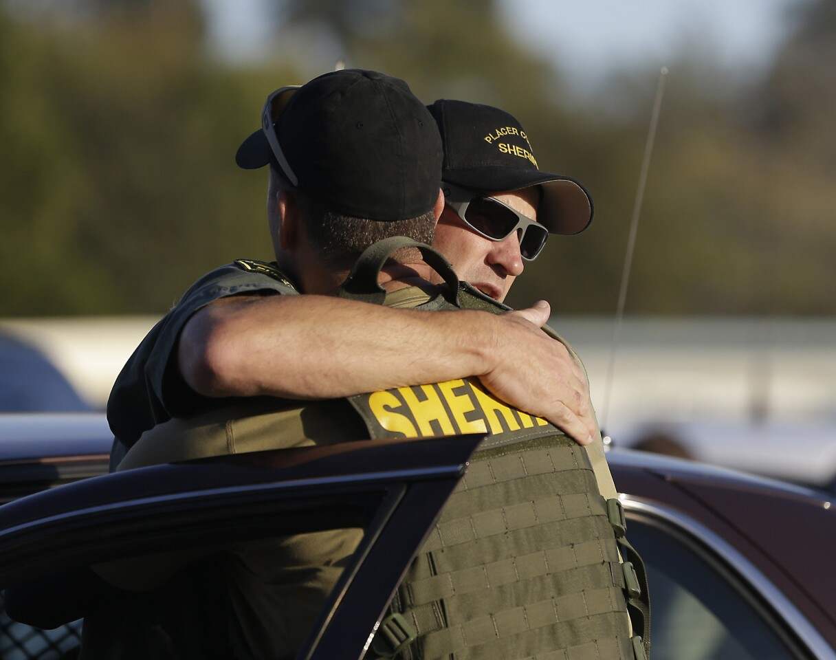 A pair of Placer County sheriff's deputies embrace after a suspect was arrested who allegedly shot and killed two deputes, wounded a third and a bystander during a series of shootings that spanned across two California counties.