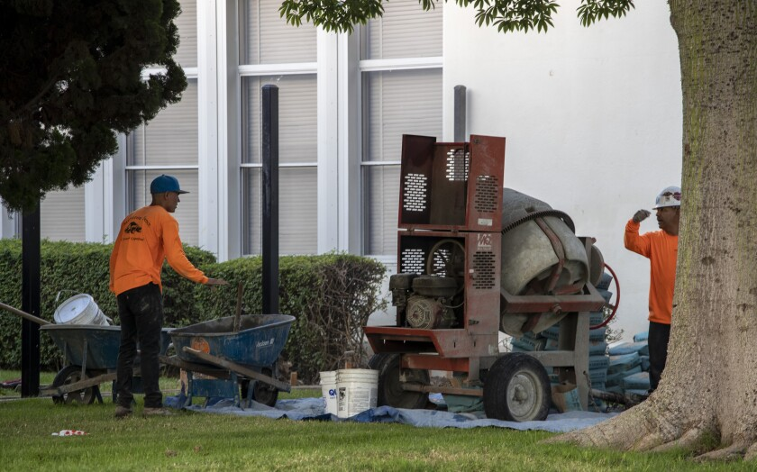 Construction workers mix concrete for a new fence around Fremont Elementary School