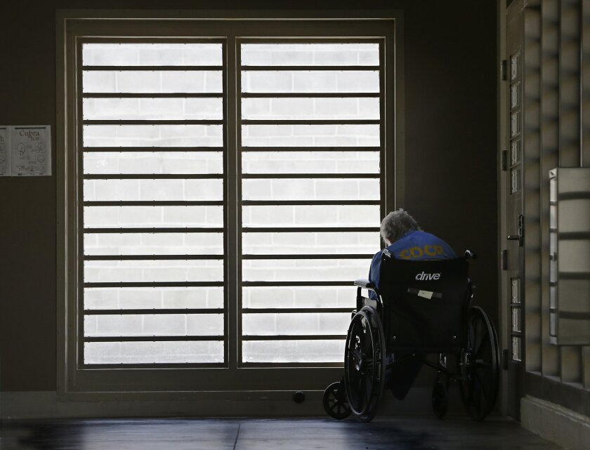 In this Thursday, July 24, 2014 photo, an inmate sits by a window at the mental health unit at the California Department of Corrections and Rehabilitation's Stockton Health Facility in Stockton, Calif. The California Association of Psychiatric Technicians union says that employees at the facility w