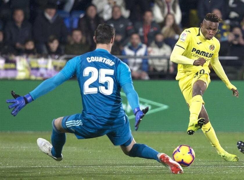 El centrocampista nigeriano del Villarreal Samuel Chukwueze (d) dispara a puerta ante el portero belga Thibaut Courtois, del Real Madrid, durante el partido aplazado de la jornada 17 de Liga en Primera División que Villarreal y Real Madrid disputan esta noche en el estadio de la Cerámica. EFE