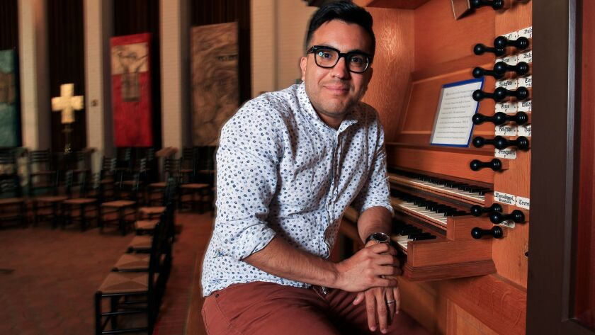 Ruben Valenzuela, founder and artistic director of the Bach Collegium San Diego, sits at the organ at All Soul's Episcopal Church in Point Loma, where he is the music director.