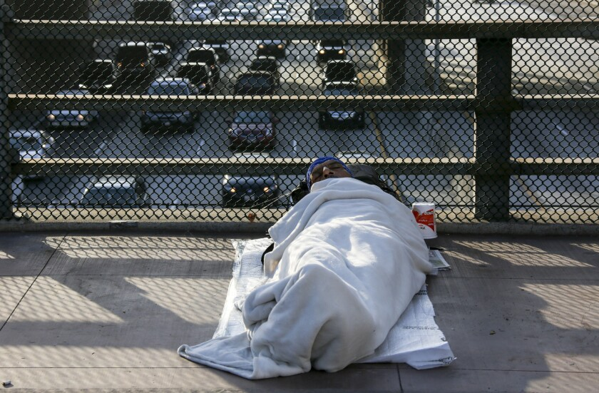 Homeless man sleeping on a bridge above the freeway in downtown L.A.