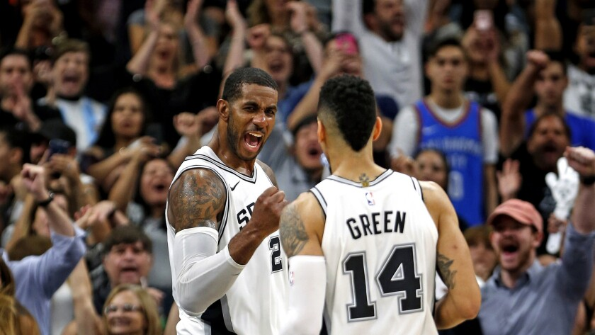 Spurs forward LaMarcus Aldridge celebrates with teammate Danny Green after defeating the Thunder on Friday night.