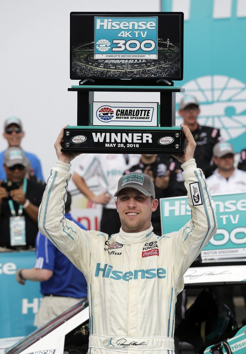 Denny Hamlin raises the trophy in Victory Lane after winning the NASCAR Xfinity series auto race at Charlotte Motor Speedway in Concord, N.C., Saturday, May 28, 2016. (AP Photo/Chuck Burton)