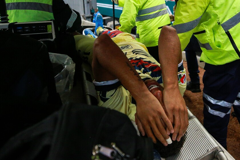 Club America's Giovani Dos Santos is carted off the field during a game against Guadalajara on Sept. 28 in Mexico City.