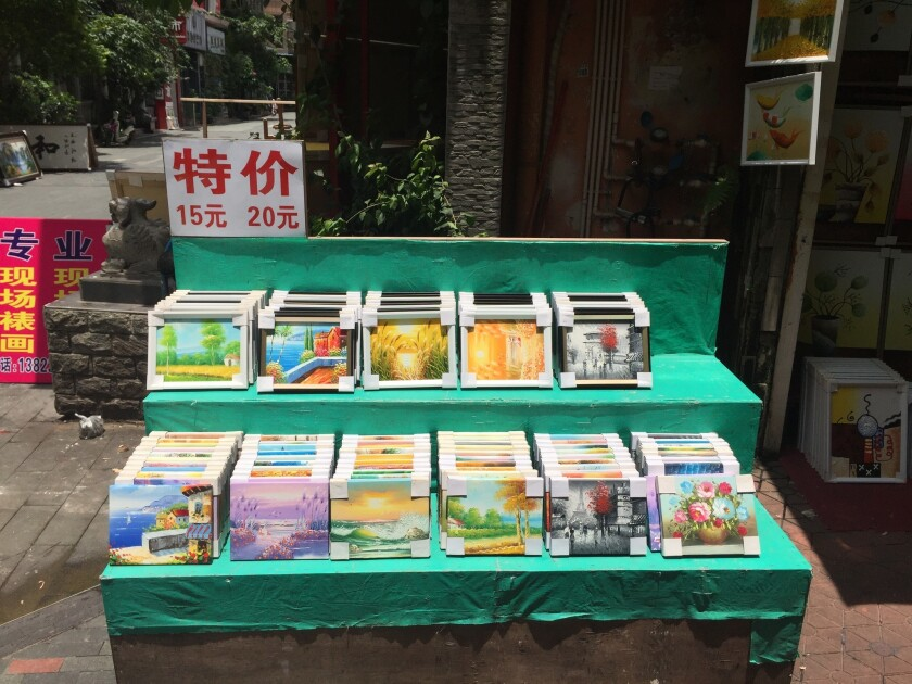 Shown are pictures for sale in Dafen Oil Painting Village in China. The sign says the paintings cost 15 to 20 yuan each, about $2 to $3.