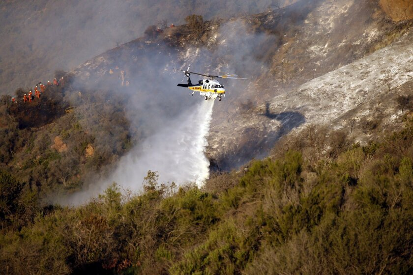 A firefighting helicopter makes a water drop on a brush fire in Malibu, Calif., on Thursday, Feb. 25, 2016. Light winds are assisting helicopter crews making water drops over the fire in steep, inaccessible terrain north of Pacific Coast Highway. Several roads are shut down. The cause is under investigation. (Al Seib /Los Angeles Times via AP) NO FORNS; NO SALES; MAGS OUT; ORANGE COUNTY REGISTER OUT; LOS ANGELES DAILY NEWS OUT; INLAND VALLEY DAILY BULLETIN OUT; MANDATORY CREDIT, TV OUT
