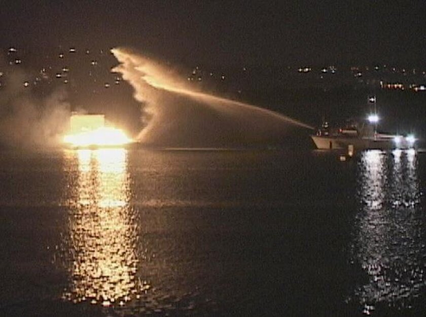 A San Diego Lifeguard fire boat extinguishes a fire on SeaWorld's fireworks barge.