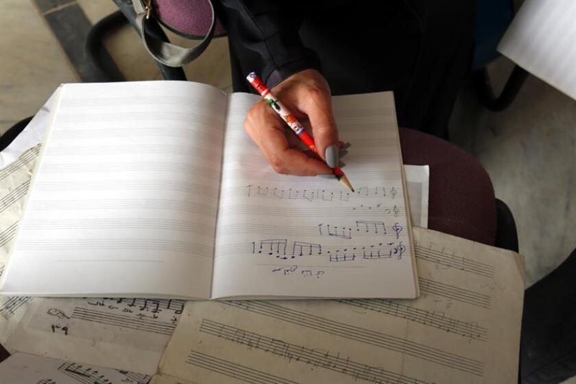 Una estudiante yemení de música escribe una nota musical durante una sesión de práctica en un centro cultural en Sana'a, Yemen, el 27 de febrero de 2018. EFE/Archivo