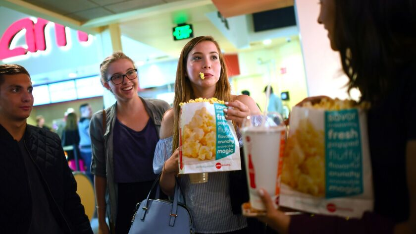 Friends Max Dodd, left, Morgan Gerlach, Natalie Gold and Audrey Hattori grab popcorn before a screen