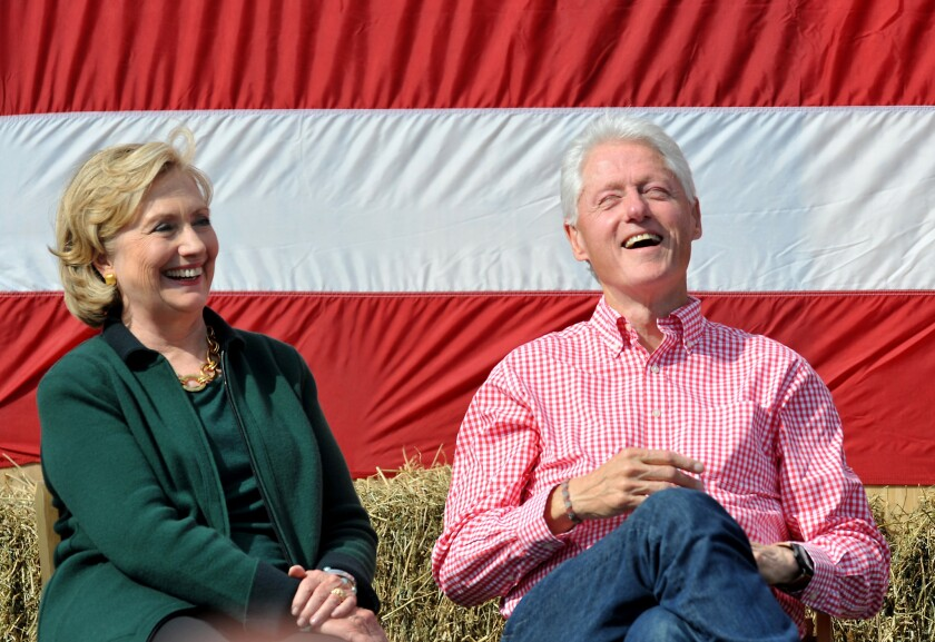 Former President Bill Clinton and his wife former Secretary of State Hillary Rodham Clinton laugh during a speech by then-Sen. Tom Harkin in Iowa in 2014.