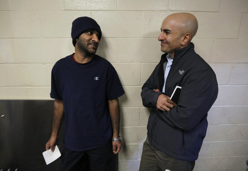 Neel Kashkari, right, who is exploring a possible run for governor in 2014, talks with Farhad Hakim, 31, at Loaves and Fishes homeless shelter in Sacramento, Calif., Wednesday, Dec. 4, 2013. Kashkari, a former U.S. Treasury staffer who headed up the federal bank bailout program, says he is a Republ
