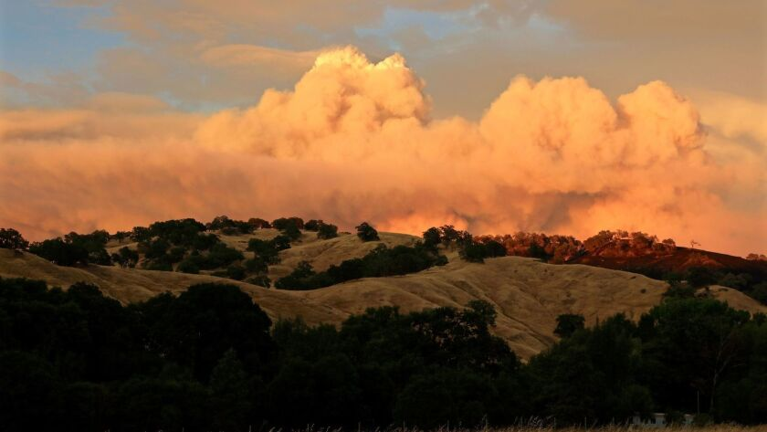 Sunset strikes the smoke clouds from the Ranch fire portion of the Mendocino complex fires near the Mendocino National Forest on Sunday.