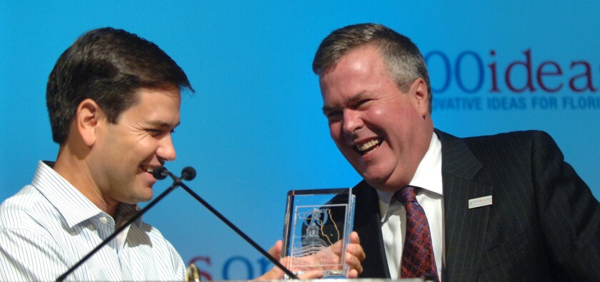 A photo taken Aug. 11, 2006 shows then-Gov. Jeb Bush laughing as incoming Florida House Speaker Marco Rubio presents him with an award at a Republican policy conference Rubio organized in Orlando, Fla.