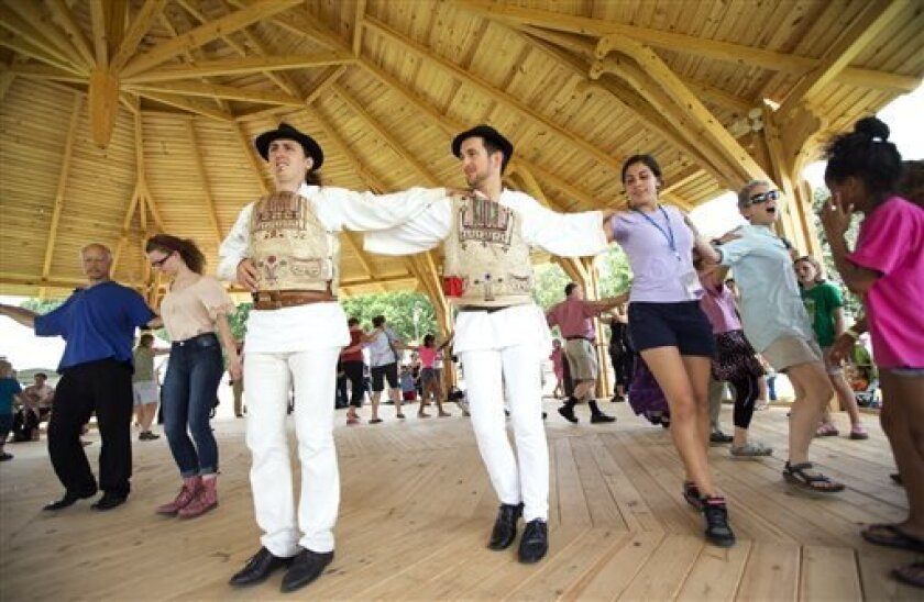 "In this July 3, 2013 photo, Hungarians, from left, Andre Csaba and Lorand Bodor, lead festival visitors in dancing the Hejsza, a Hungarian folk dance, in the Dance Barn, at the 47th annual Smithsonian Folklife Festival on the National Mall in Washington. Hungarian structures are part of the ""Hungarian Roots to Revival"" program in this year's Smithsonian Folklife Festival _ and a personal thrill for the team of carpenters from Hungary who arrived a month prior to the festival to construct the 23-"