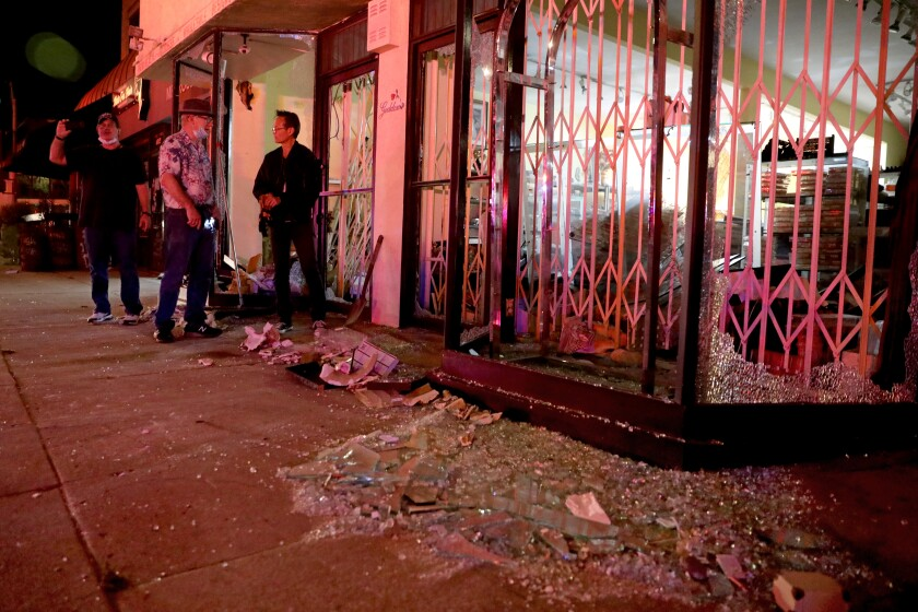 Shop owners assess the damage after looters and vandals ransack businesses along Melrose Avenue on Saturday.