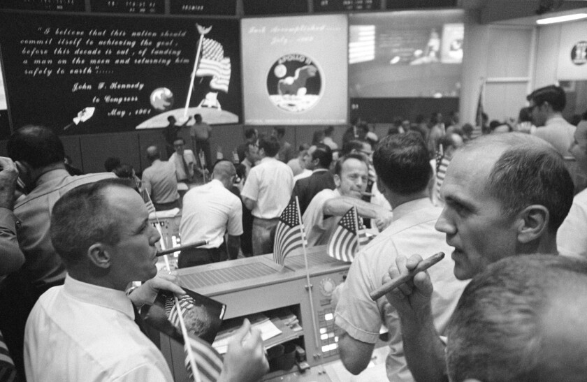 Gerry Griffin, left, and Tom McMullen enjoy celebratory cigars at Mission Control in Houston after the Apollo 11 crew's successful return to Earth in July 1969.