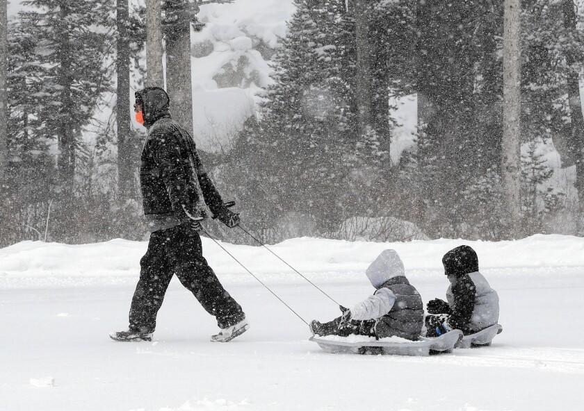 Mel Turner tows his grandsons, Myles, 5, and Dylon Mike, 6, to a sledding run at the Adventure Mountain snow park near Echo Summit, Calif.