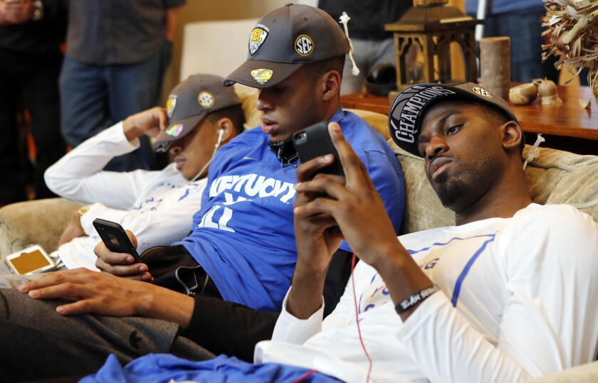 Kentucky's Tyler Ulis, left, sleeps while Skal Labissiere and Alex Poythress check their phones as other members of the men's basketball team watch the NCAA tournament selection show at the home of Coach John Calipari on Sunday.