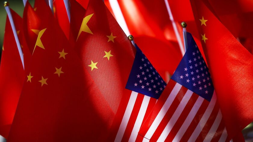 FILE - In this Sept. 16, 2018, file photo, American flags are displayed together with Chinese flags