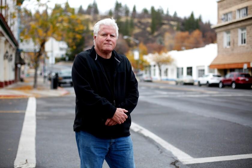 Ein Mann steht auf einer Straße in der Innenstadt mit einem Hügel voller Bäume in der Ferne.