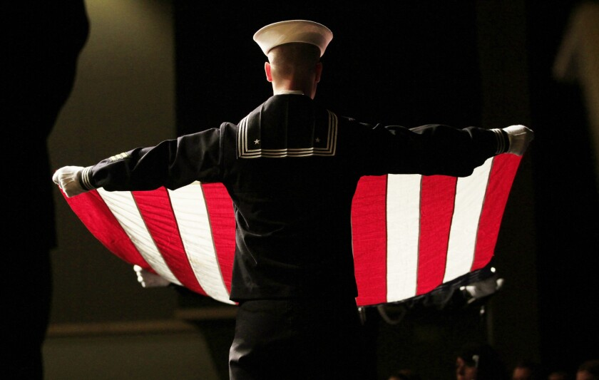 Matthew Oberg with the Navy Operation Support Center re-creates the flag-folding ceremony performed at military funerals during a Veterans Day observance Thursday at Kettle Moraine Lutheran High School in Jackson, Wis.