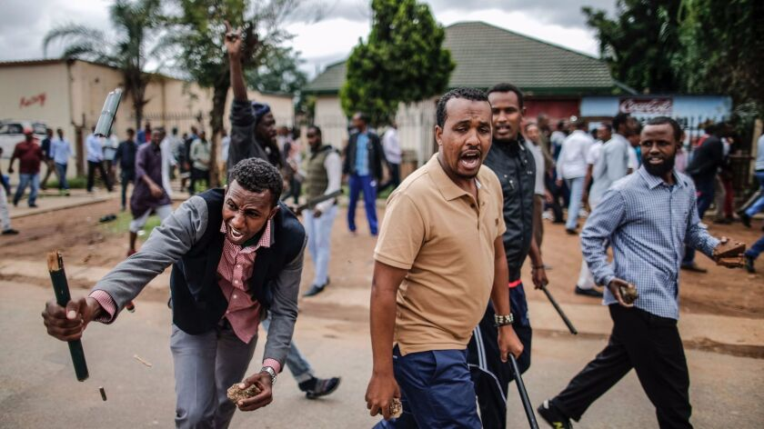 Somali migrants, fearing attack, march in the South African capital, Pretoria, on Feb. 24, 2017, armed with rocks and sticks.