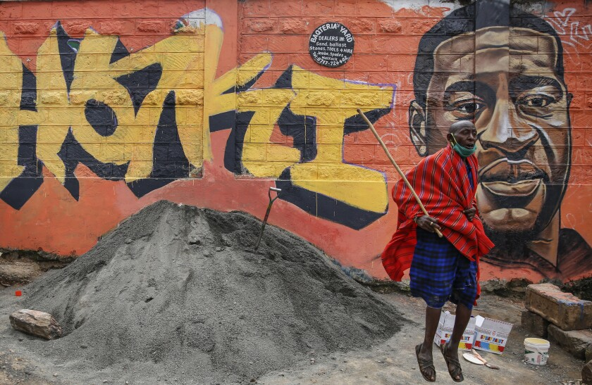 """FILE - In this Wednesday, June 3, 2020 file photo a Maasai man, who said he had seen videos on Facebook about protests in the U.S. over the death of George Floyd, jumps next to a new mural painted this week showing Floyd with the Swahili word """"Haki"""" meaning """"Justice"""", in the Kibera slum, or informal settlement, of Nairobi, Kenya. Since George Floyd's death in the U.S. state of Minnesota last week, his face has been painted on walls from Nairobi, Kenya to Idlib, Syria. Floyd's name has been inked on the shirts of soccer players and chanted by crowds from London and Cape Town to Tel Aviv and Sydney. (AP Photo/Brian Inganga, File)"""