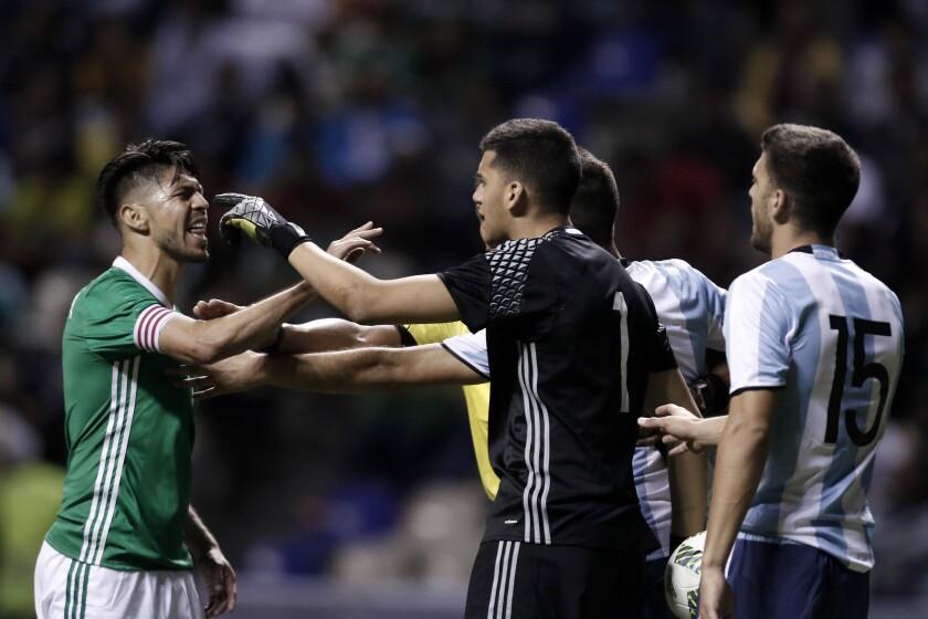 El jugador Oribe Peralta (i) de la selección Sub23 de México discute con Gerónimo Rulli (c) de Argentina hoy, jueves 28 de julio de 2016, durante un partido amistoso rumbo a los Juegos Olímpicos de Río de Janeiro 2016, en el estadio Cuauhtémoc, en Puebla (México).