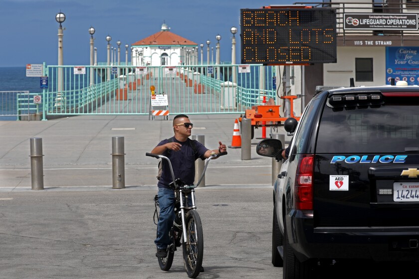 A Manhattan Beach police officer lets Michael Aranda know the bike path is closed.