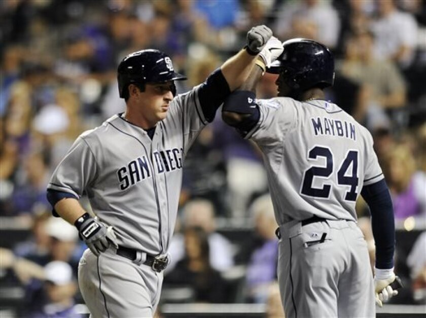 San Diego Padres Jedd Gyorko, left, is congratulated by Cameron Maybin after Gyorko hit a solo home run in the seventh inning of a baseball game against the Colorado Rockies on Thursday, June 7, 2013 in Denver. The Rockies won 10-9. (AP Photo/Chris Schneider)