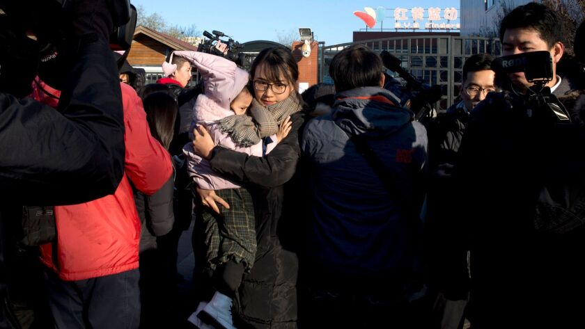 A woman leaves with a child after telling the media she came to withdraw the child from the RYB kindergarten in Beijing on Friday, Nov. 24, 2017. The school has suspended three teachers.