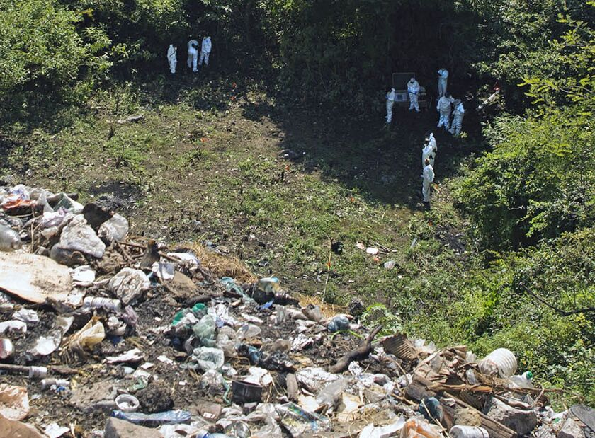 Forensic examiners look for human remains below a garbage-strewn hillside in the densely forested mountains on the outskirts of Cocula, Mexico.