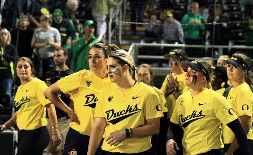 Oregon players watch as UCLA players celebrate a 2-0 win in the deciding game of the NCAA softball tournament super regional in Eugene, Ore., Sunday, May 29, 2016. (Collin Andrew/The Register-Guard via AP)