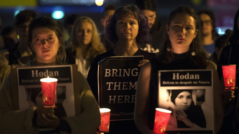 People in Sydney hold a vigil honoring two refugees who set themselves on fire in the remote island of Nauru, where Australia is indefinitely detaining hundreds of asylum seekers.