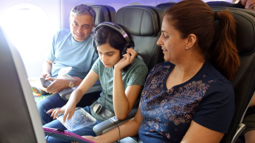 A young girl is buckled in with her parents for the (Ready Set Fly) on-plane practice which simulate