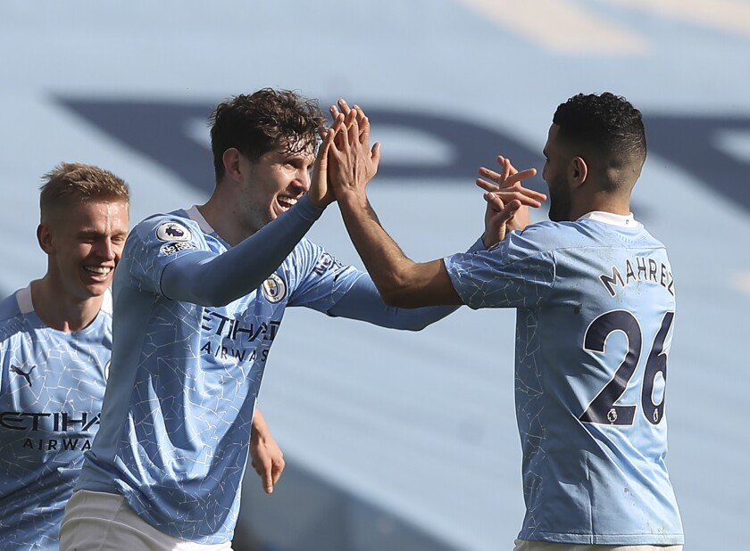 Manchester City's John Stones, front left, celebrates with teammates after scoring his side's second goal during the English Premier League soccer match between Manchester City and West Ham United at the Etihad stadium in Manchester, England, Saturday, Feb. 27, 2021. (Martin Rickett/Pool via AP)