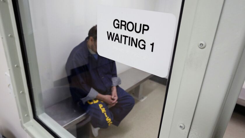 In this Feb. 14, 2013, photo, an inmate waits in a holding room at a mental health treatment unit at the California Medical Facility in Vacaville, Calif.
