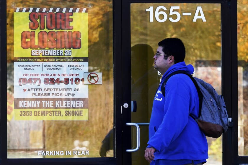 A man walks past a closed store in Wilmette, Ill., amid the coronavirus pandemic.