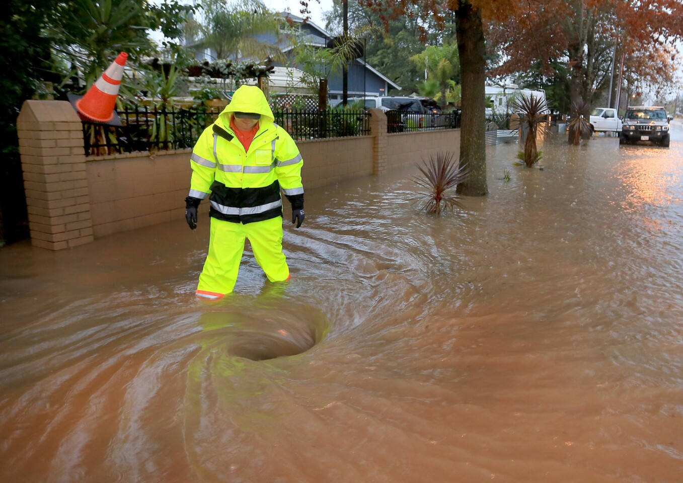 Scott Taylor of Windsor Public Works opens a manhole to help drainage along Old Redwood Highway in Windsor. A powerful storm churned down the West Coast on Thursday, bringing strong gales and much-needed rain and snow.