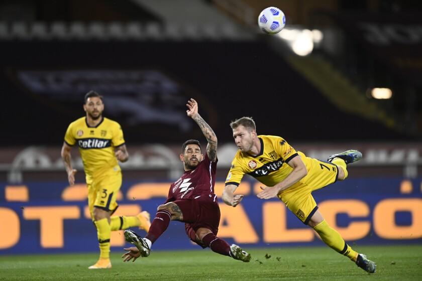 Unos jugadores van por el balón durante el partido de la Serie A italiana entre el Torino y el Parma en Turín, Italia, el lunes 3 de mayo de 2021. (Fabio Ferrari/LaPresse vía AP)