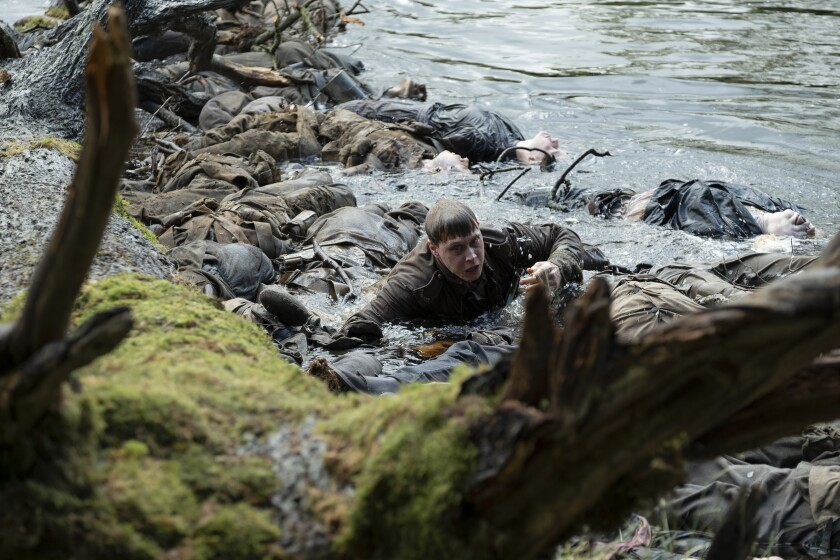 "George MacKay emerges from the river in ""1917."""