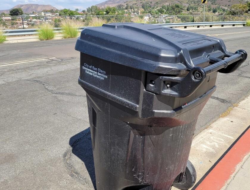 A City of San Diego trash can awaits pickup on a city street.