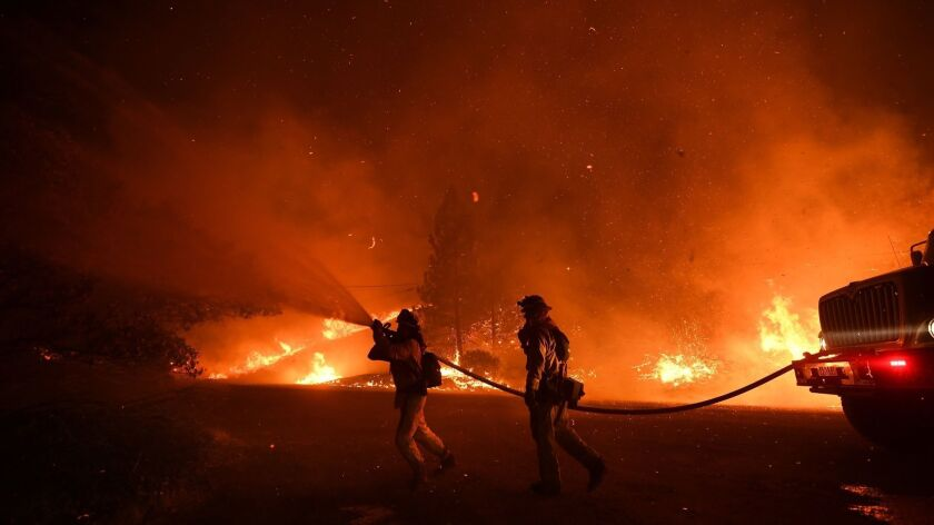 Firefighters continued to battle wildfires throughout California on Tuesday. Here, Cal Fire crews fight the Delta fire as it burned north of Redding on Friday.