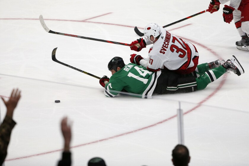Carolina Hurricanes right wing Andrei Svechnikov (37) pulls down Dallas Stars left wing Jamie Benn (14) during the third period of an NHL hockey game in Dallas, Tuesday, Feb. 11, 2020. Dallas defeated Carolina 4-1. (AP Photo/Michael Ainsworth)