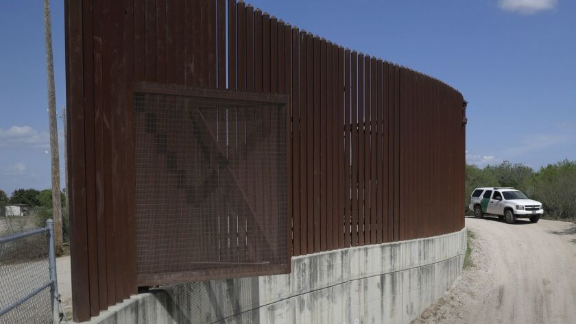 A U.S. Customs and Border Patrol vehicle passes along a section of border levee wall in Hidalgo, Texas, last year.