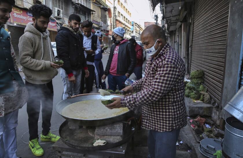 Un vendedor ambulante,  sirve un pudin de trigo y mantequilla en su puesto en Jammu, India