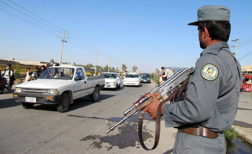 Afghan security officials conduct roadside checks Feb. 9 as part of increased security measures following reports that Mullah Abdul Rauf, a former Taliban commander who reportedly defected to the Islamic State movement, was killed in drone attack.