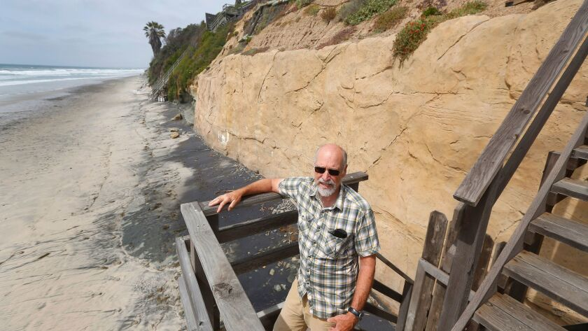 Tom Frick stands on the staircase that runs from his oceanfront house to the beach in Encinitas.